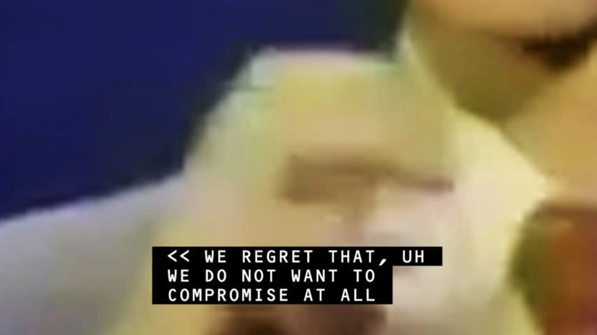 """still image from Jenny Brady video 'Receiver', blurry image of hand with overlaid caption that says, """"We regret that, um we do not want to compromise at all"""""""