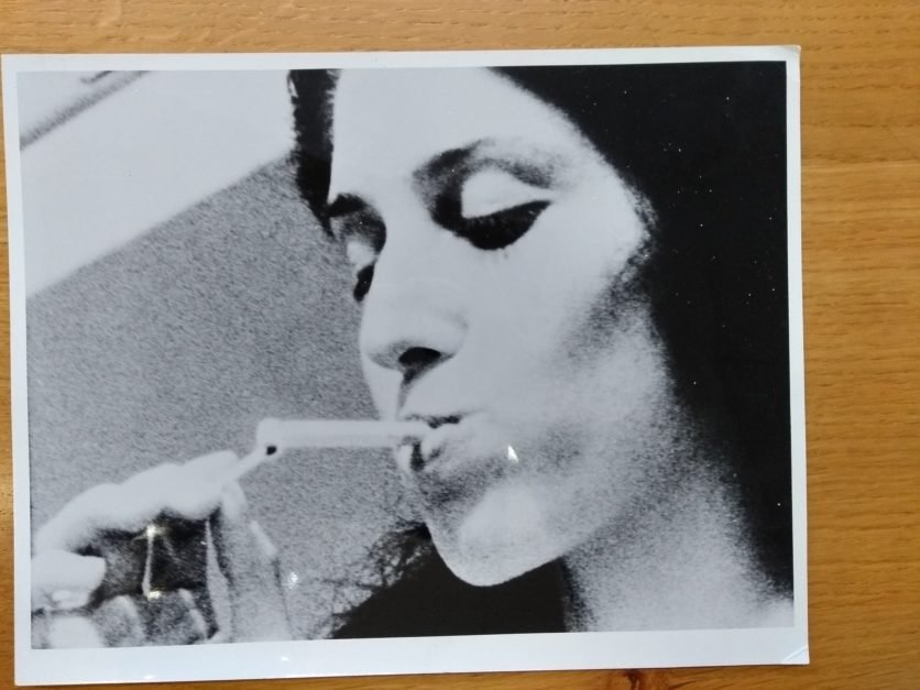 A B&W photograph on a wooden surface. In the picture is a close up of a woman lighting a cigarette with a match.
