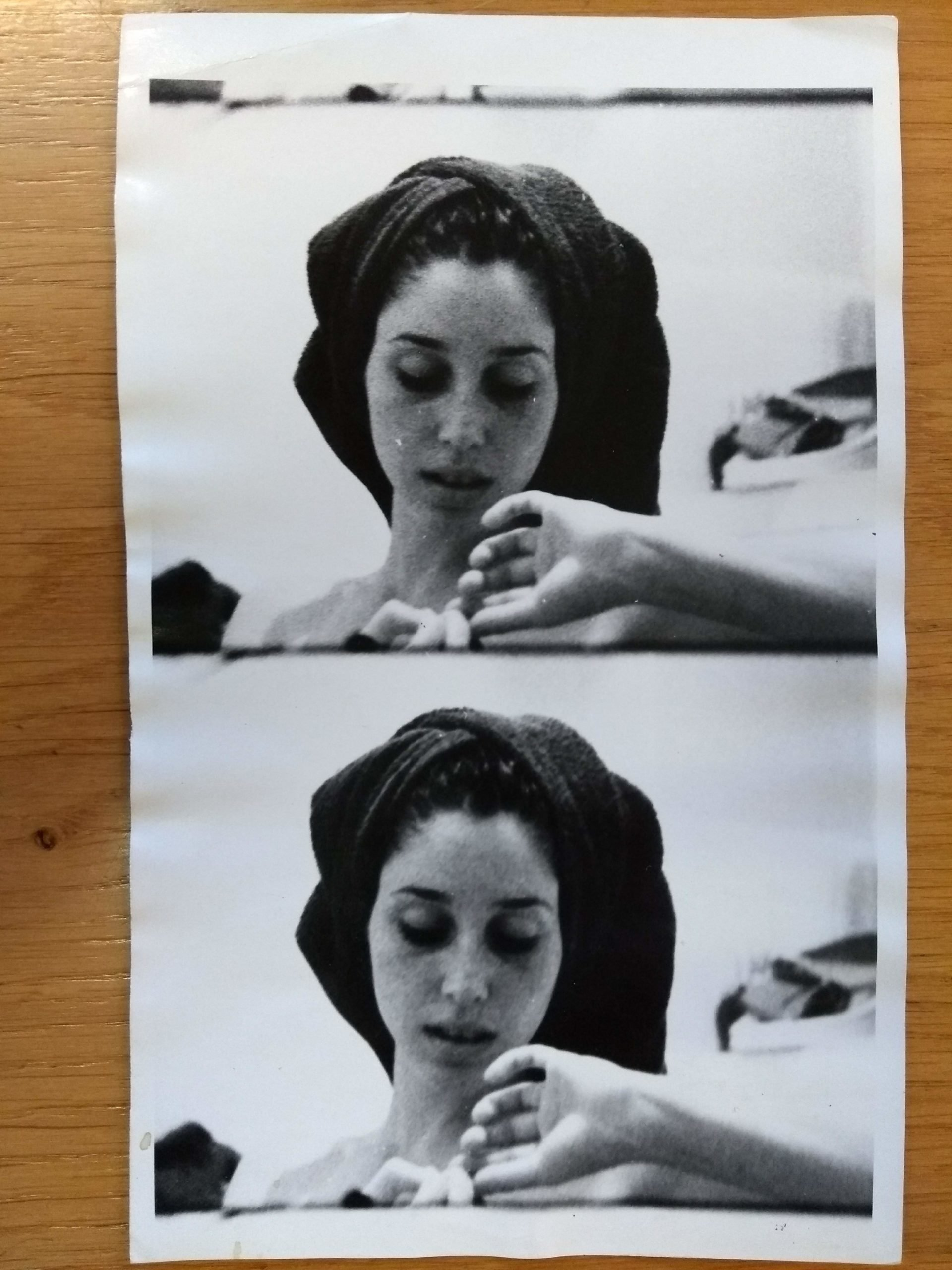 A B&W split-frame photograph of a white woman pinching nails with her hair wrapped with a towel. The same image in each frame.