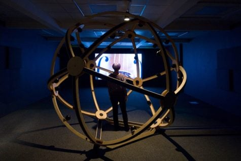 A geodesic globe made with metal structure sits in a dark space. Through this an image of a string instrument is projected on the back wall.